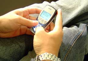 Teenager sending text message on cell phone